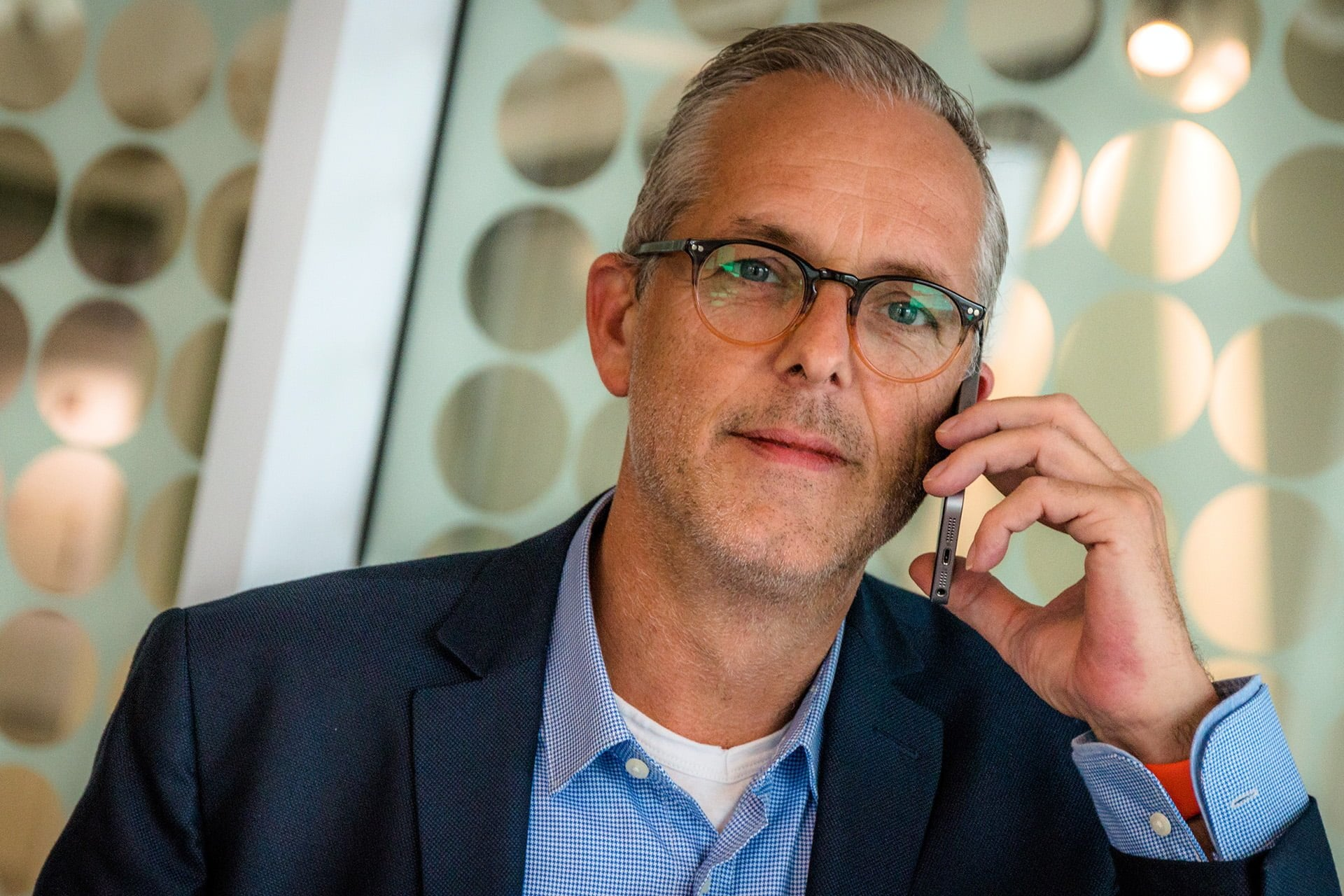 man wearing glasses holding smartphone to his ear listening