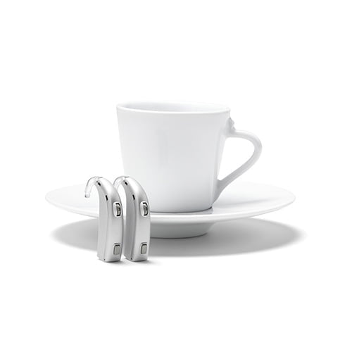 two behind the ear (BTE) hearing aids standing on end in front of a coffee cup on a saucer