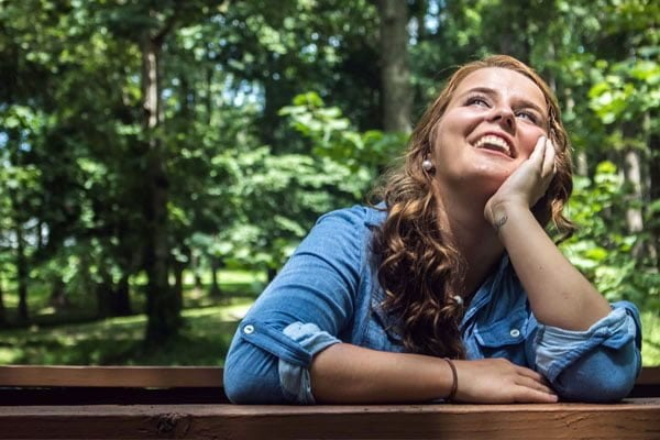 happy female sitting at picnic table smiling at the sky in the woods