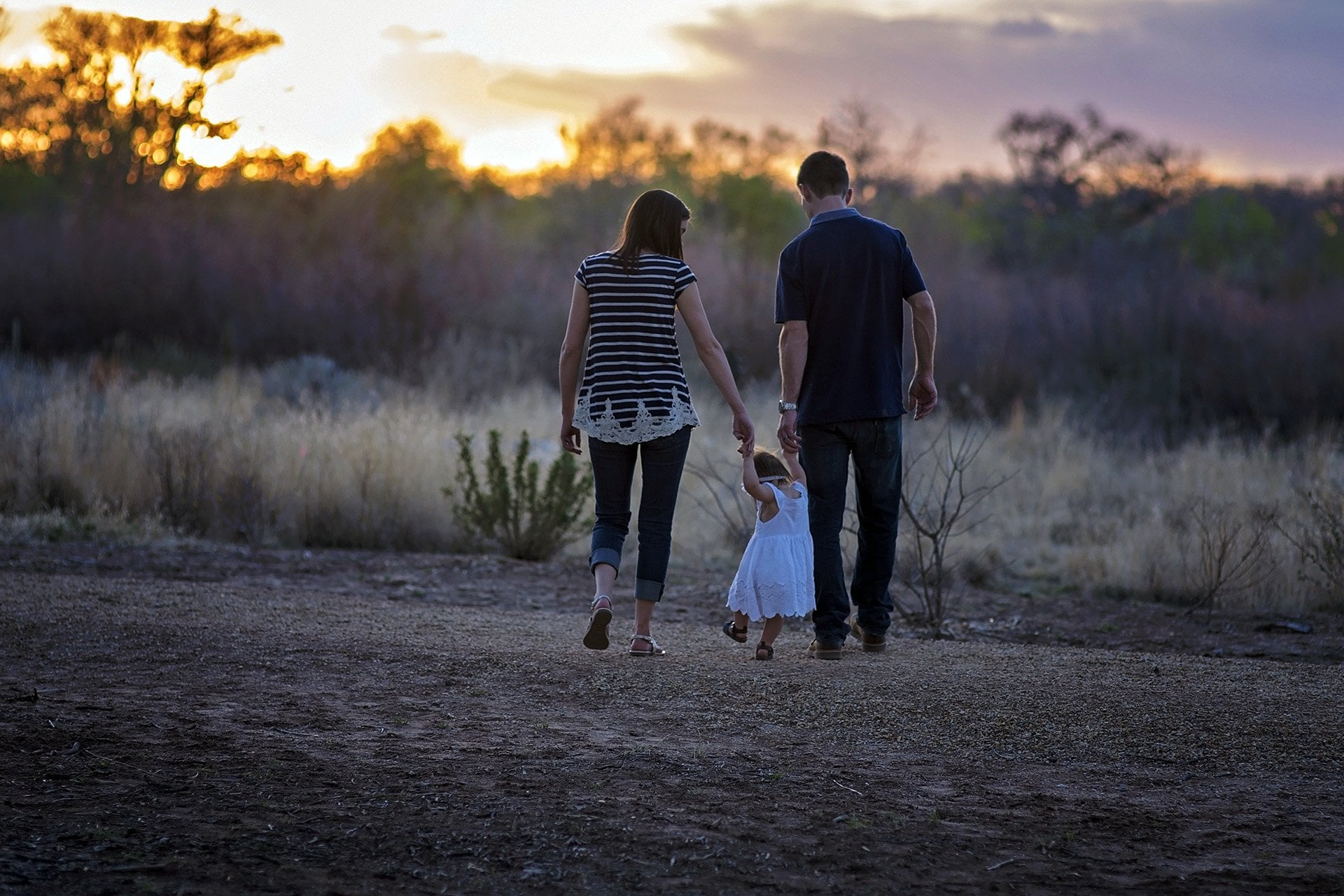 Mother and father walking with young daughter in a field
